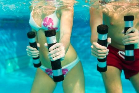 gimnasia: Fitness - un hombre joven pareja y la mujer la pr�ctica de deportes y la gimnasia o aer�bic acu�tico bajo el agua en la piscina o spa con mancuernas Foto de archivo