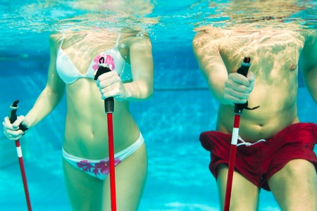 Fitness - a young couple man and woman doing sports and\ gymnastics or water aerobics under water in swimming pool or spa\ with Nordic walking sticks