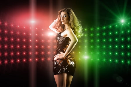 Beautiful young girl or woman dancing in a club disco to the music, lots of lights visible photo