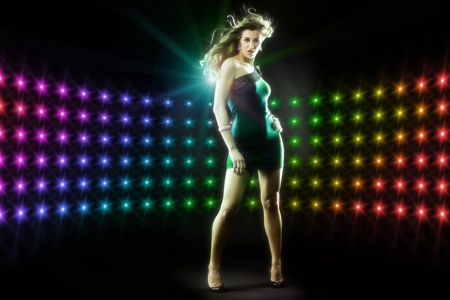 Beautiful young girl or woman dancing in a club disco to the music, lots of lights visible Stock Photo - 12718824