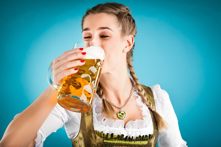 Young woman in traditional Bavarian clothes - dirndl or tracht with a beer stein and beer photo