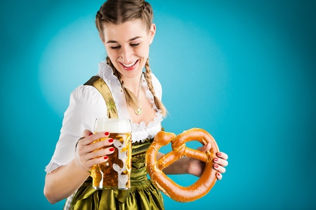 Young woman in traditional Bavarian clothes - dirndl or tracht with a beer stein and beer and brezel photo