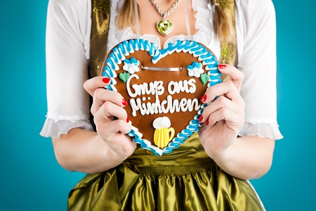 Young woman in traditional Bavarian clothes - dirndl or tracht with a gingerbread souvenir heart photo