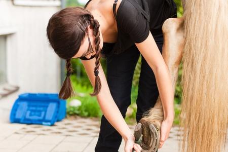 hooves: Teenage girl is grooming her horse outdoors Stock Photo