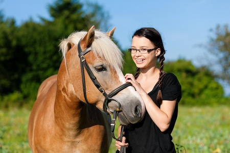 Teenage girl standing on a meadow in summer with her horse photo