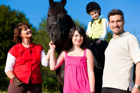 Family with children posing with a horse, one child riding the animal   photo