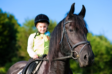 equitation: Little girl riding in summer with her horse   Stock Photo