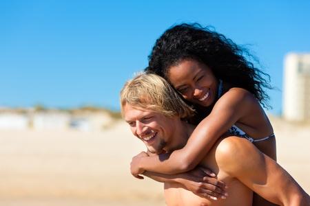 paar - man en vrouw - op het strand met veel plezier, is de man die de vrouw pak terug