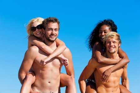 Four friends - men and women - on the beach having lots of fun, the men carrying the women pack back Stock Photo - 12719162