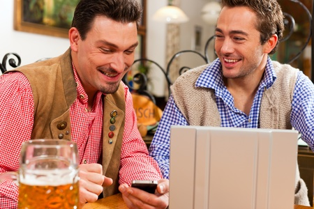 Two friends in Bavarian pub in traditional clothes sitting on a table in a pub with laptop photo