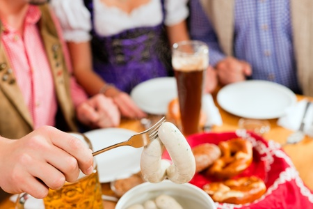 group of young men and women in traditional Bavarian Tracht having a breakfast with white veal sausage, pretzel, and beer photo