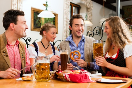 veal sausage: group of young men and women in traditional Bavarian Tracht having a breakfast with white veal sausage, pretzel, and beer Stock Photo