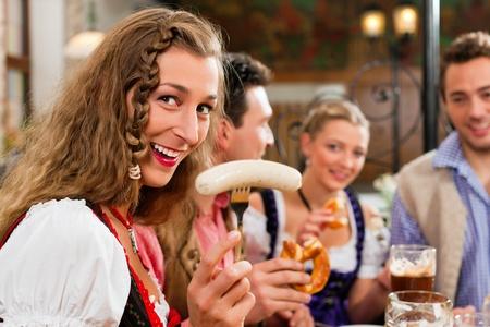 saucisse: groupe de jeunes hommes et femmes en Bavi�re Tracht traditionnelle ayant un petit d�jeuner avec des saucisses de veau blanc, bretzel, et de la bi�re