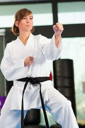 artes marciales: Mujer en el entrenamiento de artes marciales en un gimnasio, ella está usando un cinturón negro Foto de archivo