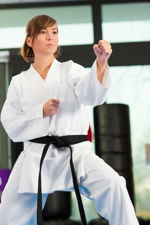 black belt: Woman in martial art training in a gym, she is wearing a black belt