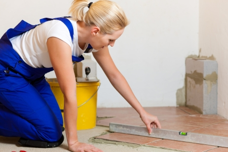 doityourself: Female construction worker is tiling at home; she is presumably a do-it-yourself