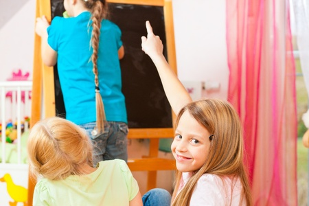 Children - sisters - playing school in their room Stock Photo - 12719325