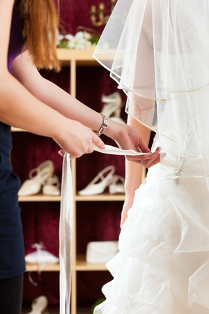 Bride at the clothes shop for wedding dresses; she is choosing a dress and the designer is assisting her photo