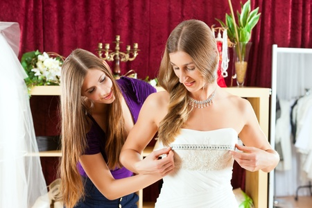 tailored: Bride at the clothes shop for wedding dresses; she is choosing a dress and the designer is assisting her Stock Photo