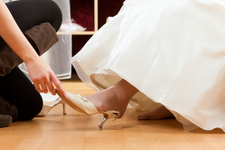 fitting: Bride at the clothes shop for wedding dresses; she is choosing a dress is fitting bridal shoes Stock Photo