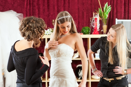 Bride at the clothes shop for wedding dresses; she is choosing a dress and the designer is assisting her Stock Photo
