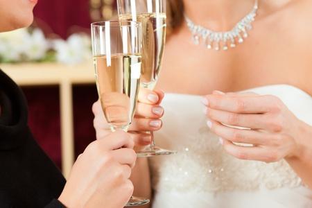 clinking: Novia en la tienda de ropa para vestidos de novia, ella es la elecci�n de un vestido y se tintineo de copas con sus amigos