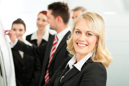 training consultant: Business - team in an office; a colleague is standing in front of the flipchart, one female colleague is looking in to the camera