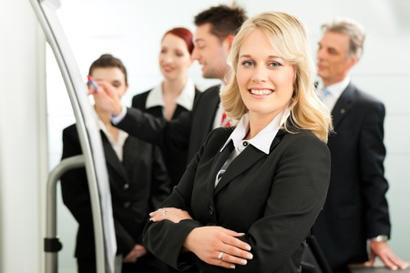 Business - team in an office; a colleague is standing in front of the flipchart, one female colleague is looking in to the camera photo