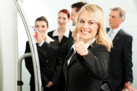 thumps up: Business - team in an office; a colleague is standing in front of the flipchart, one female colleague is looking in to the camera