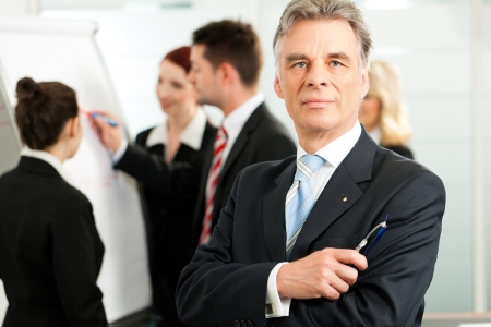 business advice: Business - team in an office; the senior executive is standing in front