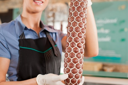 Cropped image of smiling female professional holding sausage photo