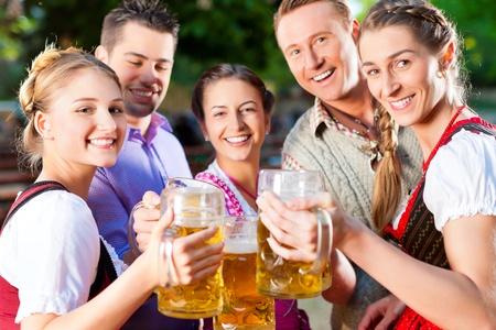 beer garden: In Beer garden - friends in Lederhosen drinking a fresh beer in Bavaria, Germany