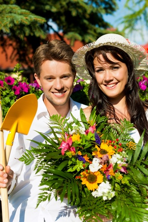 Happy couple gardening in summer with tools, she is wearing a hat Stock Photo - 12719323