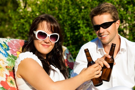 Couple in love drinking beer in summer in the garden and enjoy photo