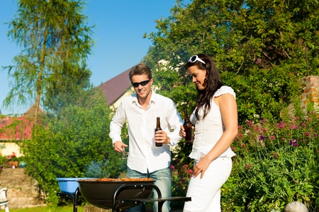 barbecue party: Couple - man and woman - doing the barbeque together in their garden in summer Stock Photo