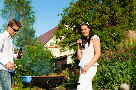 Couple - man and woman - doing the barbeque together in their garden in summer photo