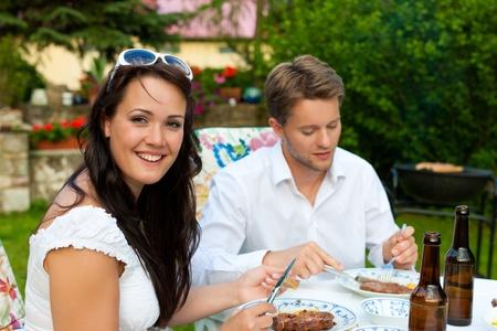 pareja comiendo: Pareja - hombre y mujer - haciendo la barbacoa juntos en su jardín en verano