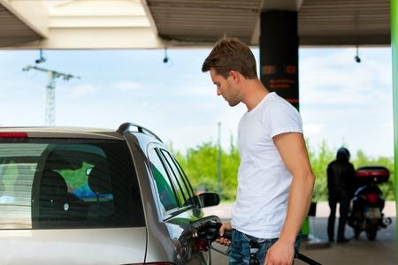 gasolinera: Llene el dep�sito del coche en una gasolinera, el hombre la celebraci�n de la llave