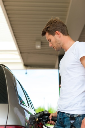 Refuel the car on a gas station; man holding the tap photo