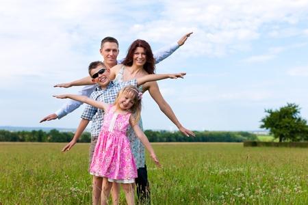 Glückliche Familie - Mutter, Vater, Kinder - stehend auf einer Wiese im Sommer unter blauem Himmel