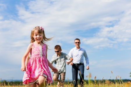 father children: Happy family - mother, father, children - playing on a meadow in summer under blue sky