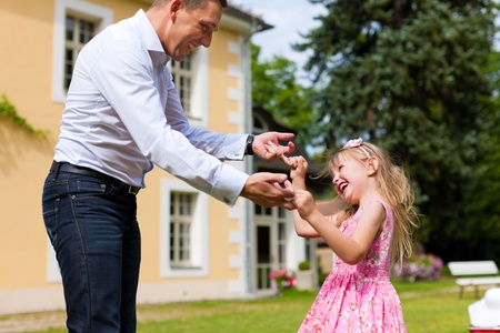 affairs: Family affairs - father and daughter playing in summer; he is dancing with her in the garden in front of the house Stock Photo