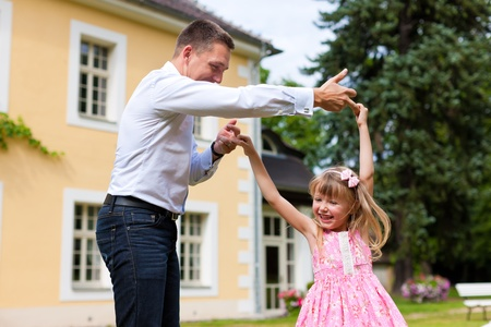 Family affairs - father and daughter playing in summer; he is dancing with her in the garden in front of the house photo