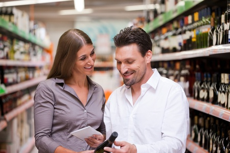 shoppers: Happy young couple smiling while shopping for wine together at supermarket Stock Photo