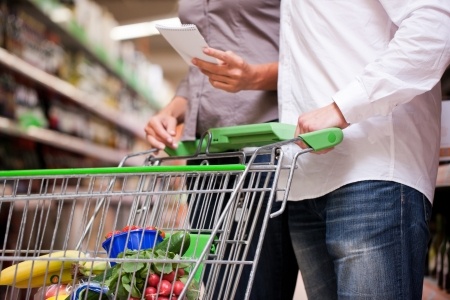 supermarket shopping: Cropped image of couple shopping groceries together with trolley at supermarket Stock Photo