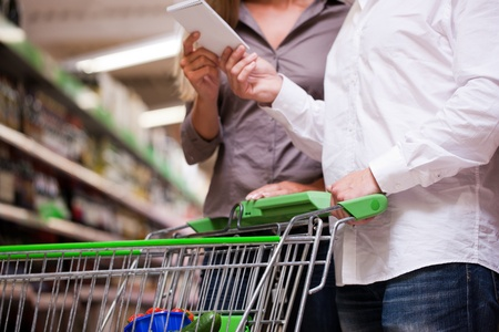 Young couple shopping together with trolley at supermarket photo