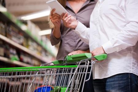 Pareja joven de compras junto con el carro en el supermercado