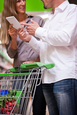 Young couple deciding with spiral notebook while shopping at supermarket photo