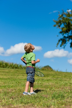 sunlit: Family - little boy playing badminton outdoors on a summer day