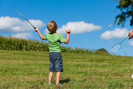 Family - little boy playing badminton outdoors on a summer day photo
